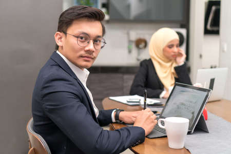 Asian malay executive working at home with laptop looking at the camera