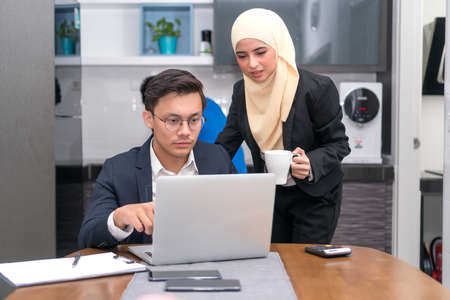 Asian malay executive working at home with laptop discussing Zdjęcie Seryjne