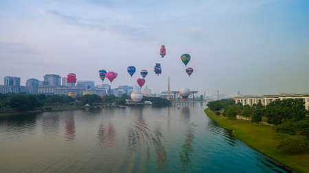 PUTRAJAYA, MALAYSIA - MARCH 29, 2019: The beautiful of multi shaped of hot air balloons floating over sunrise skies at the 10th Putrajaya International Hot Air Balloon Fiesta 2019