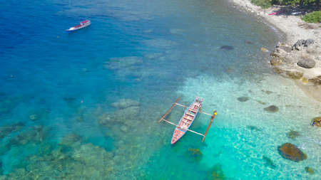 Traditional boat with Beautiful nature of blue sea sand and Turquoise color water waves at Atauro Island, Timor Leste Banque d'images