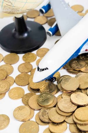 Toy plane with coins, travel concept