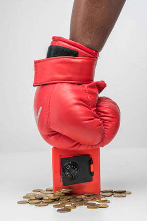 Hand wearing boxing glove and punch the red safe box Imagens
