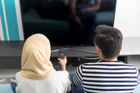 Young Malay Couple at the Sofa watching tv together
