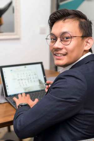 Happy Smiling Asian Malay executive working with laptop Stockfoto