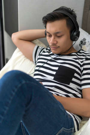 Young Malay guy looking at the phone relaxing at the bed listening to the music