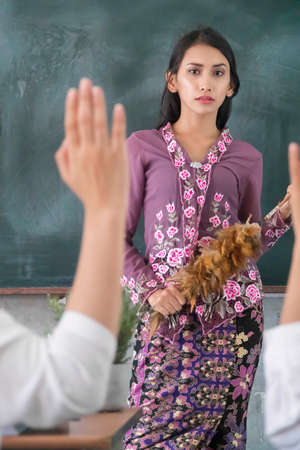 Beautiful Malay Teacher wearing traditional cloth at school and student raise hand Imagens