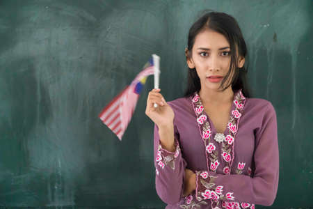 Beautiful Malay Teacher wearing traditional cloth at school holding Malaysian flag Imagens