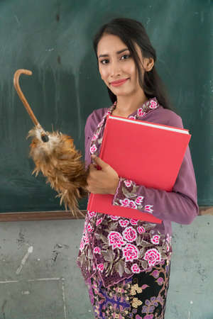 Beautiful Malay Teacher wearing traditional cloth at school holding book and feather duster