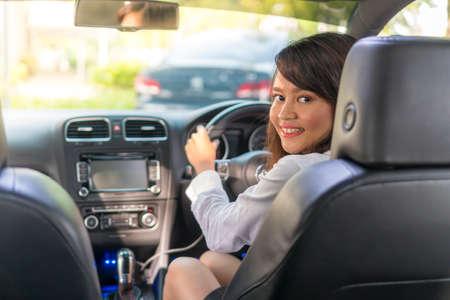 Schattig Aziatisch meisje in de auto glimlachend e-hailing concept Stockfoto