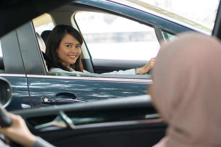 Cute Asian girl inside the car smiling and looking at the camera