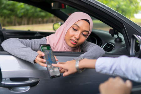 Cute Asian girl wearing hijab holding mobile phone asking direction
