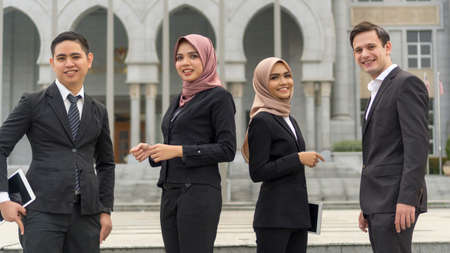 A group of young mixed Asian Executive at the wearing suit standing and smile to camera