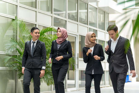 A group of young mixed Asian Executive at the corridor walking and talking to each other Imagens