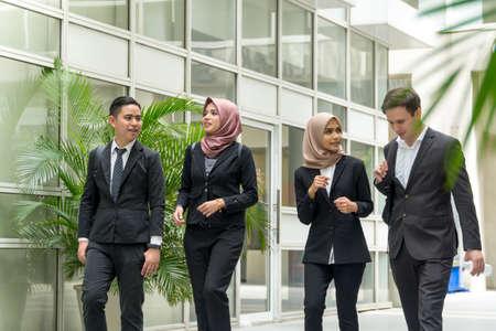 Eine Gruppe junger gemischter asiatischer Führungskräfte auf dem Korridor, die miteinander spazieren gehen und sich unterhalten? Standard-Bild