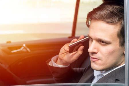 E-Hailing concept, young executive talking thru the phone looking thru window