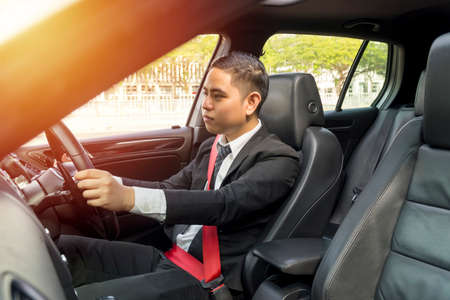 E-Hailing Concept, giovane uomo asiatico alla guida di un'auto con cintura di sicurezza