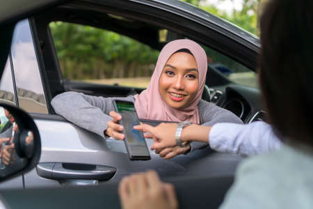 Cute Asian girl inside the car smiling and looking at the camera, e-hailing concept Stock Photo