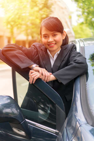 Cute Asian girl outside the car smiling and looking at the camera, e-hailing concept