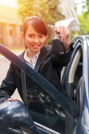 Cute Asian girl holding car keys and smiling e-hailing concept Stockfoto