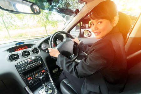 Cute Asian girl inside the car smiling and looking at the camera, e-hailing concept