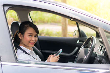 E-hailing concept, Cute Asian girl inside the car smiling and looking at the camera holding smartphone