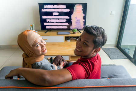 Lifestyle concept, couple watching tv at the sofa looking at the camera