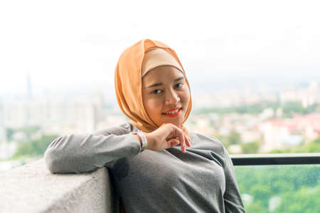 Portraiture of cute malay muslim wearing hijab outdoor at the balcony Stock Photo