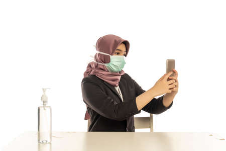 Business Lifestyle, Cute Malay Woman wearing hijab, face mask using mobile phone 版權商用圖片