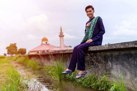 Asian guy wearing traditional cloth outdoor sitting at the canal with mosque background