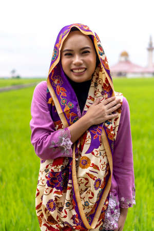 Asian malay lady wearing traditional cloth outdoor with mosque background 版權商用圖片