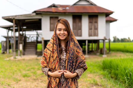 Asian Malay lady wearing traditional cloth outdoor at the old abandon house