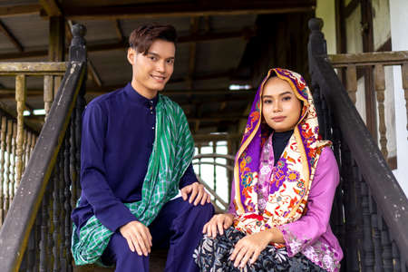 Asian couple wearing traditional cloth sitting on the bench