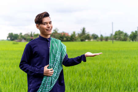 Malaysian guy wearing traditional cloth outdoor smiling to the camera