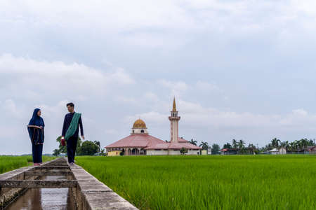 Malay couple wearing traditional cloth outdoor walking at the canal with mosque background