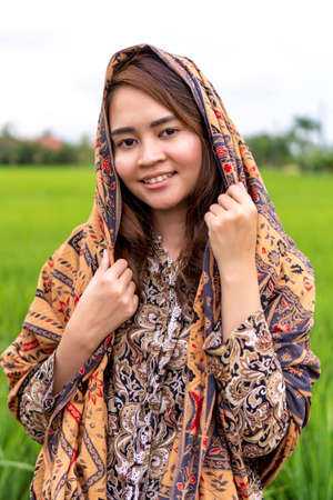 Asian Malay lady wearing traditional cloth outdoor over the green paddy background