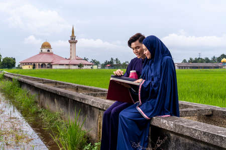 Malay couple wearing traditional cloth outdoor sitting at the canal with mosque background 版權商用圖片