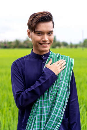 Malaysian guy wearing traditional cloth outdoor hand to the chest 版權商用圖片