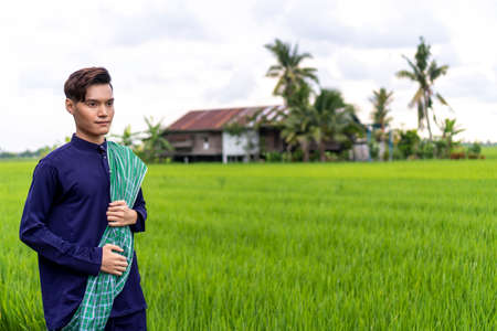 Asian Malay guy wearing traditional cloth outdoor over the green paddy background 版權商用圖片