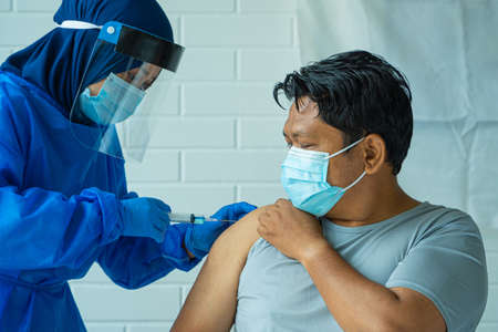 Pandemic concept, average Asian Malay Man taking Vaccine and look scared being injected