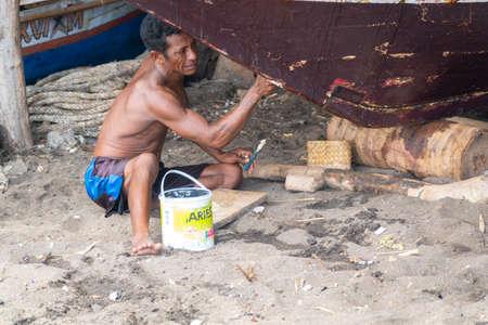 LAMALERA, NUSA TENGGARA, INDONESIA - DEC 13, 2018: Adults male repairing a traditional boat at lamalera, Indonesia Publikacyjne