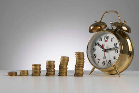 Finance concept, gold coin with alarm clock represent time is above the essence