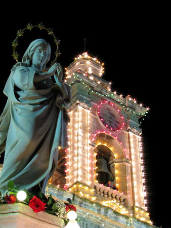 immaculate: A marble statue of The Immaculate Conception with the belfry of the church in Cospicua, Malta  Stock Photo