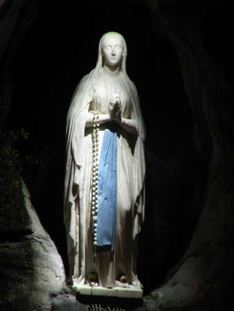 The statue of Our Lady of Lourdes at the exact place where Our Lady appeared to Saint Bernadette in the Grotto of Massabielle at Lourdes in France.