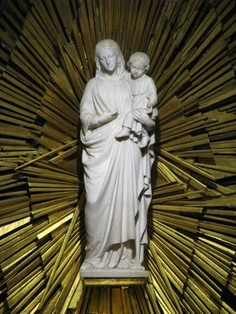 favours: A statue of Our Lady in the Crypt of the Marian Shrine of Lourdes in France. The walls of the corridor and nave of this Crypt are lined with small marble plaques, known as ex voto plaques, donated in thanks of spiritual favours received Editorial