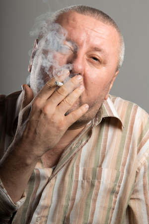cigarette smoke: Close-up of man face holding cigarette and smoking