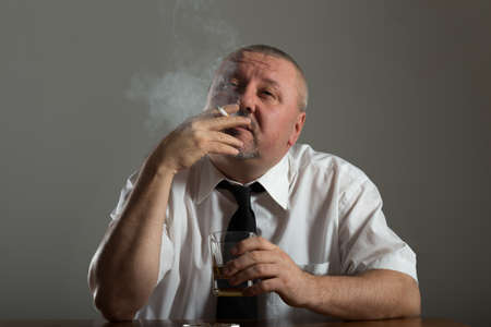 lonely person: Businessman drinking alcohol and smoking cigarette