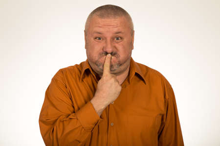 shh: Man in orange shirt with a gesture of shh on white background