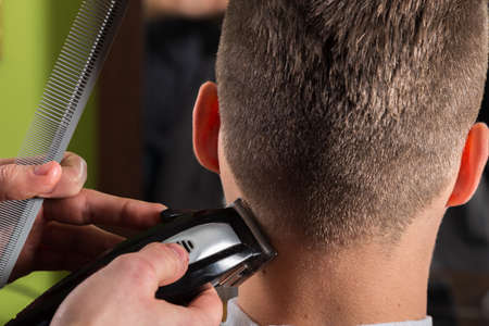 cutting hair: Hairdresser cutting clients hair with an electric hair clipper at beauty salon