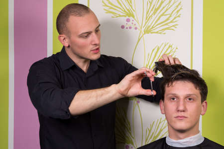 haircutting: Mens hairstyling and haircutting with hair clipper and scissor in a barber shop or hair salon. Stock Photo