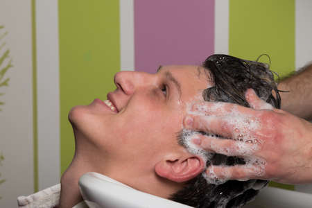 beauty parlour: Portrait of handsome male client getting his hair washed at salon